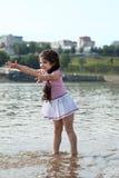 滑稽的小女孩戏剧用水飞溅 免版税库存照片