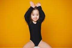 滑稽的小女孩用人工做兔宝宝耳朵在橙色背景 拷贝空间 免版税库存照片