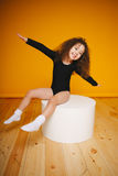 滑稽的小女孩用人工做飞机翼在橙色背景 拷贝空间 库存照片