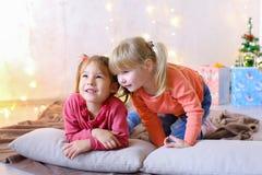 滑稽的小女孩笑并且谈话,摆在说谎在地板和  库存照片
