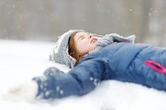 滑稽的小女孩获得乐趣在冬天公园 免版税库存照片