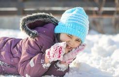 滑稽的小女孩获得乐趣在美丽的冬天公园在降雪期间 免版税库存图片