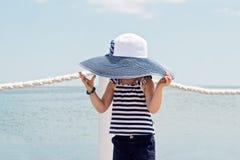 滑稽的小女孩(3年)在海滩的大帽子的 免版税库存图片