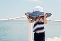 滑稽的小女孩(3年)在海滩的大帽子的 免版税库存照片