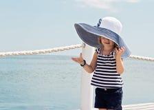 滑稽的小女孩(3年)在海滩的大帽子的 图库摄影