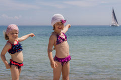 滑稽的小女孩(姐妹)在旗鱼点的海滩的 库存照片