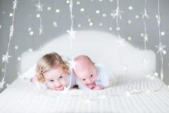滑稽的小孩女孩和她新出生的一起放松小的兄弟 免版税图库摄影