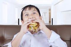 滑稽的小男孩享用汉堡包 免版税图库摄影