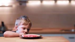 滑稽的小男孩坐厨房和尝试把脚放在桌上,笑 愉快男性尖叫喜悦 股票录像