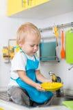 滑稽的小男孩坐厨房用桌和洗涤的盘 库存照片