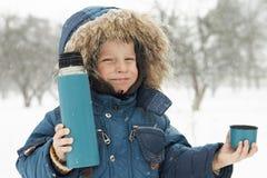 滑稽的小男孩邀请喝从热水瓶的热的茶 免版税库存照片