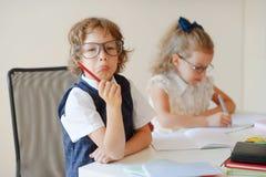 滑稽的小的学生坐在一张书桌 库存图片