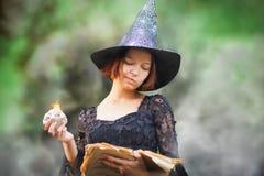 年轻滑稽的巫婆铸件咒语,绿色雾aroung她,万圣夜概念 免版税图库摄影