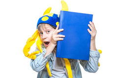 戴滑稽的帽子的逗人喜爱的恼怒的时髦的孩子拿着一本非常大蓝皮书 免版税图库摄影