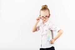 滑稽的微笑的小女孩仿效一位严密的老师反对丝毫 免版税库存图片