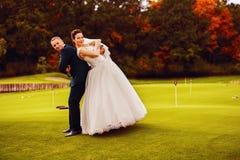 滑稽的愉快的新娘和新郎在高尔夫球调遣 免版税库存照片