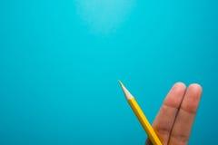 画滑稽的手指拿着黄色铅笔反对蓝色背景 概念性刺激图片 免版税库存照片