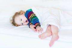滑稽的打呵欠的小孩女孩在白色床上的采取休息 免版税图库摄影