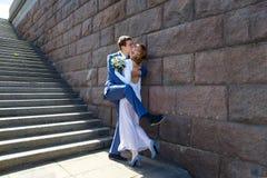 滑稽的拥抱在台阶附近的新郎和新娘在镇里 免版税图库摄影
