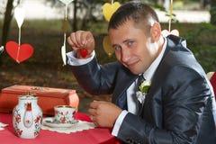 滑稽的新郎用草莓 免版税图库摄影