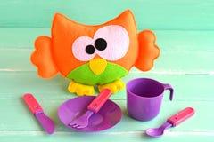 滑稽的毛毡猫头鹰玩具,在绿色木背景的儿童的碗筷 免版税图库摄影