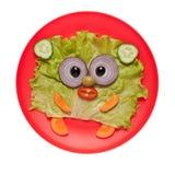 滑稽的熊由新鲜蔬菜做成在红色板材 免版税库存图片