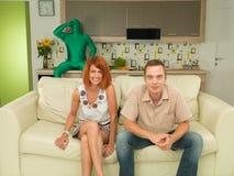 滑稽的片刻,看电视的夫妇 库存图片