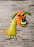 滑稽的狗由新鲜蔬菜做成在木背景 免版税库存图片