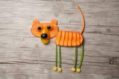 滑稽的狗由新鲜蔬菜做成在木背景 免版税库存照片