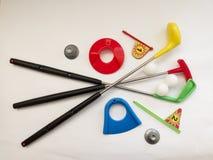 滑稽的玩具高尔夫球设置了与俱乐部、球、球机架、孔和旗子 免版税库存图片