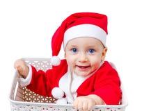 滑稽的男孩在坐在箱子的圣诞老人衣服 免版税库存照片