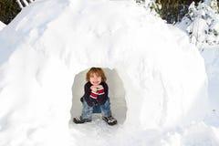 滑稽的男孩在雪园屋顶的小屋在一个晴朗的冬日 免版税库存图片