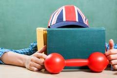 滑稽的男小学生佩带的棒球帽学会 免版税图库摄影