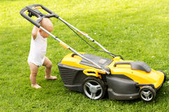 滑稽的男婴切开有grassmower的草坪 免版税库存图片