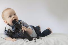 滑稽的男婴唱歌卡拉OK演唱 与话筒和耳机的说谎的婴儿孩子 做广告的概念卡拉OK演唱俱乐部 免版税库存图片