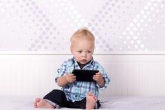 滑稽的白肤金发的在智能手机的小孩观看的动画片 使用与电话的滑稽的男婴 免版税库存照片