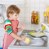 滑稽的白肤金发的孩子男孩洗涤的盘在国内厨房里 免版税库存图片