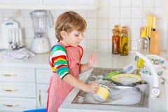 滑稽的白肤金发的孩子男孩洗涤的盘在国内厨房里 库存照片