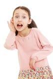 滑稽的皮包骨头的女孩投入了手到他的耳朵和 免版税图库摄影