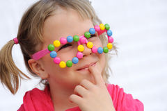 戴滑稽的眼镜的逗人喜爱的小女孩画象,装饰用五颜六色的自作聪明的人,糖果 免版税库存照片