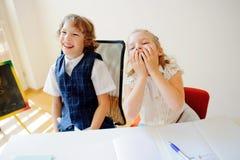 滑稽的矮小的学童,男孩和女孩,坐在一张书桌 图库摄影