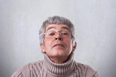 滑稽的祖父特写镜头愉快地看通过镜片的玻璃的获得乐趣 有一个年长的人神奇表达 免版税库存图片