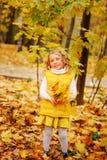 滑稽的秋天画象愉快小孩女孩走室外 免版税库存照片