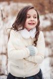 滑稽的逗人喜爱的儿童女孩在冬天森林里 免版税图库摄影