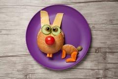 滑稽的野兔由面包、乳酪和菜做成在板材和桌 免版税库存图片