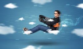滑稽的驾驶在云彩概念之间的racedriver年轻人 免版税库存图片