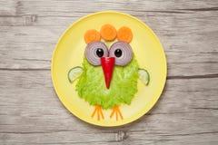 滑稽的鸡由菜做成在板材和书桌 库存照片