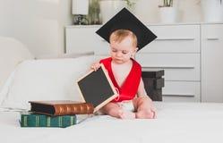 滑稽的10个月拿着书的黑毕业盖帽的婴孩 免版税图库摄影