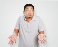滑稽的年轻亚洲人耸肩姿态 库存图片