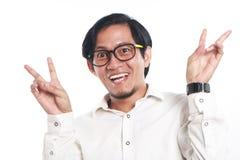 滑稽的年轻亚洲商人看了非常愉快 库存照片